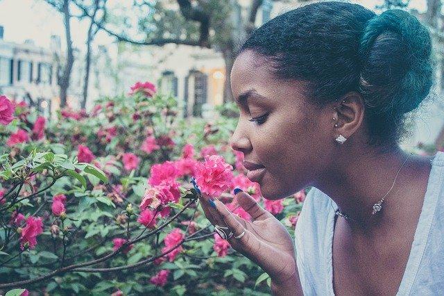 Girl smelling flowers. 5,4,3,2,1 sensory awareness exercise